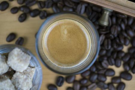 Tasse schaumiger heißer Kaffee mit Bohnen und kristallisierten Würfelzucker von oben betrachtet mit Fokus auf die Oberfläche des Getränks