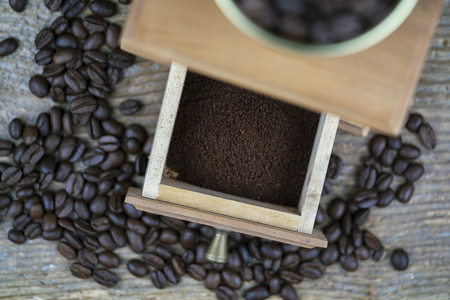 Grinder and coffee beans viewed from above with focus to the open drawer showing the freshly ground powder ready to percolate for coffee Standard-Bild