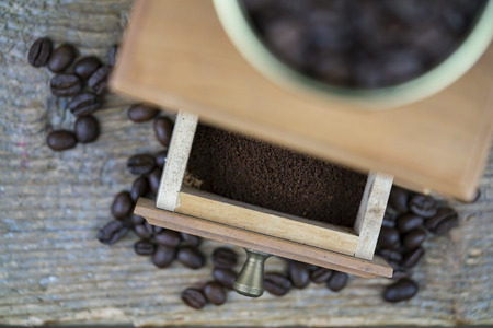 Coffee grinder viewed from above with focus to the open drawer with ground beans ready to make a fresh cup of coffee