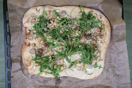 Baked pizza pie with greens on kraft baking paper over pan, close-up from above view