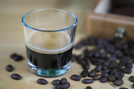 Glass of fresh aromatic espresso coffee surrounded by roasted beans with a grinder in the background