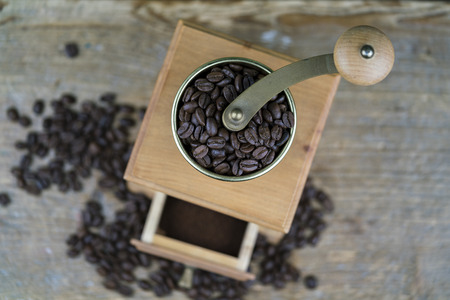 Manual coffee grinder full of fresh roasted beans viewed from above in a rustic kitchen