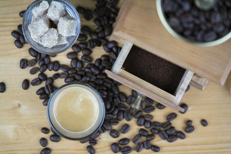 Kaffeemühle mit Espresso- und Zuckerwürfeln diente in den kleinen Gläsern, die von oben genanntem mit Fokus zum offenen Fach mit Grundbohnen angesehen wurden