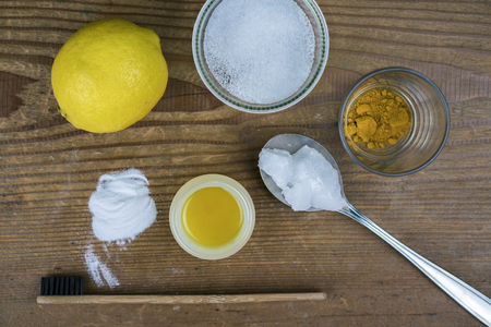 DIY toothpaste with ingredients, lemon, coconut oil, turmeric, baking soda, Xylitol and bamboo toothbrush