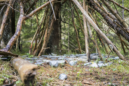 Stones arranged below a tent of branches arranged in a wigwam shape viewed low angle outdoors in a clearing in a forest