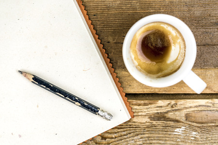 Cup of strong coffee with an old worn pencil and notepad on a rustic wood table viewed from above Standard-Bild