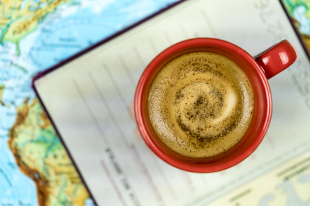 Freshly brewed cup of frothy espresso coffee and a passport on a map viewed from above in a concept of world travel and vacations