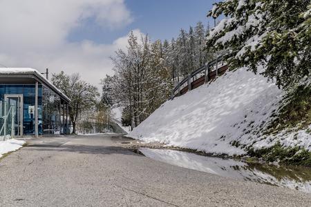 Schnee deckte Damm über einer Teerstraße mit dem Glas ab, das Eingang zu einem Zugschutz in einer kalten Winterlandschaft bedeckte