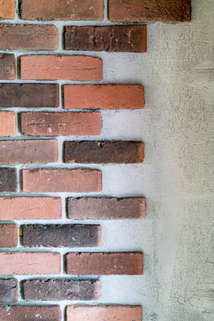 Decorative red bricks at the end of a wall with alternating lengths against exposed mortar or cement in an architectural background