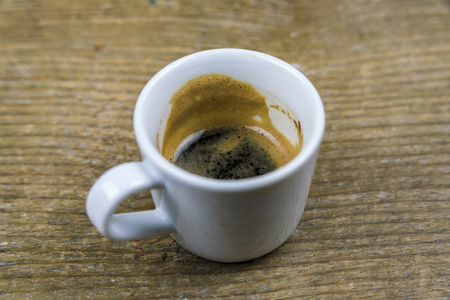 Half drunk cup of strong espresso coffee with froth on the sides viewed high angle on rustic wood Stock Photo
