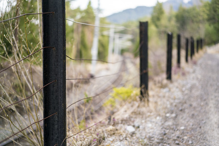 Rural fence dividing a country road from railway tracks with focus to the closest post and strands of wire over a blurred background in a receding perspective