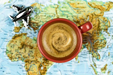 Travel planning concept with a cup of freshly brewed coffee, a small toy plane and a world map viewed from above