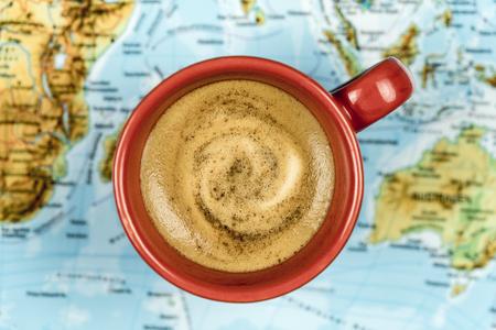 Bunte rote Schale frischer schaumiger Kaffee auf einer Weltkarte in einem Begriffsbild angesehen von oben