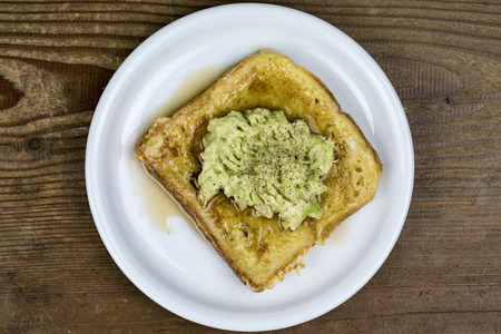 Mashed avocado pear on a slice of toast served on a white plate viewed from overhead on a wood table Standard-Bild