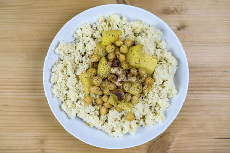 Plate filled with couscous, chickpeas and herbs over light brown wooden background