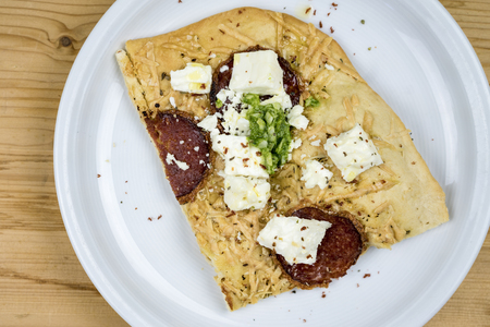Slice of homemade salami pizza with feta cheese and seasoning served on a white plate on wood