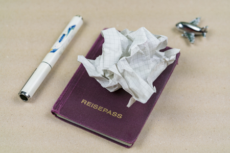 Crumpled paper on a passport with pen and toy airplane in a concept of planning an itinerary for a summer vacation or world travel