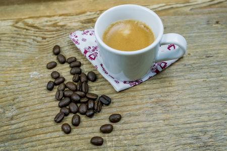 Kaffeebohnen neben einer Schale Milchkaffee gesetzt auf eine Serviette auf einen Stoff mit Kopienraum