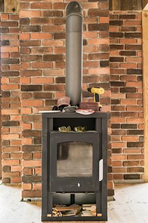 Brennender Innenofen des Holzes gegen eine Backsteinmauer, die Winterheizung für ein Haus unter Verwendung des auswechselbaren Brennstoffs zur Verfügung stellt Standard-Bild