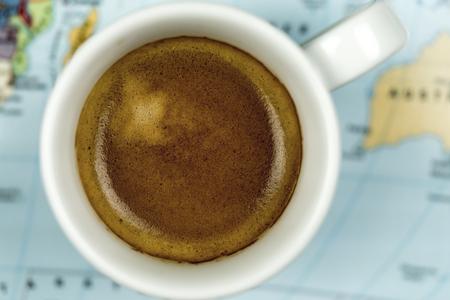 Tasse frisch gebrühten Espresso Kaffee angesehen von oben auf einem Weltkarte Hintergrund