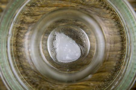 Übersteigen Sie nahe hohe Ansicht über das Cocoöl, das im Klarglasbehälter über hölzernem Hintergrund sich auflöst Standard-Bild