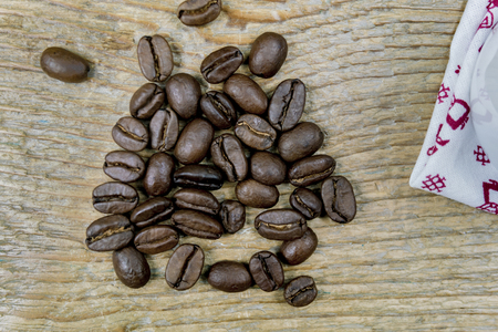 Pile of dark roast coffee beans on a wooden table viewed from above Фото со стока