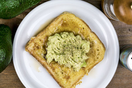 Mashed fresh avocado pear on a slice of toast with salt and pepper seasoning viewed from above on a white plate with ingredients