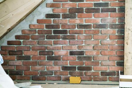 Dekorative Interieur Sichtmauerwerk mit Mörtel unter dem Winkel eines Holzbalkens in einem architektonischen Hintergrund