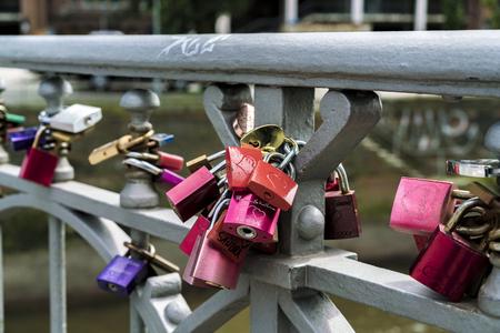 Colorful padlocks fixed at bridge balustrade as symbol of love Editorial