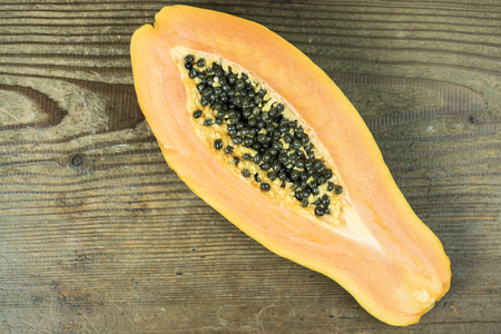 High angle view of papaya cut in half against wooden background