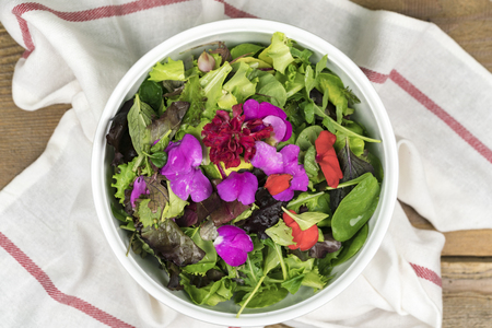 High angle view of mixed salad with eatable flowers in bowl standing on dishcloth Standard-Bild