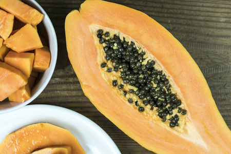 High angle view of papaya cut in half with small pieces in bowl against wooden background Standard-Bild