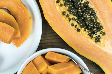 Close up view of papaya cut in half with black seeds next to small pieces in bowl against wooden background Standard-Bild