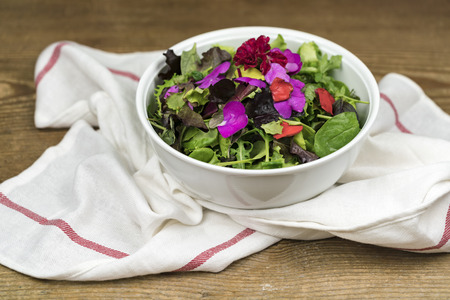 Bowl of mixed salad with edible flowers standing on dishcloth