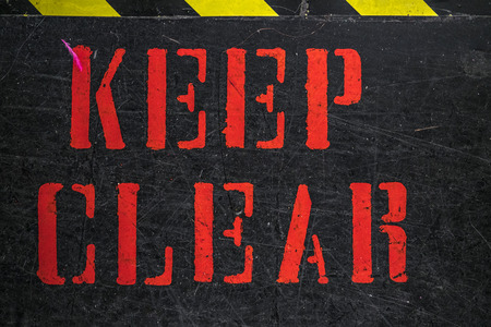Keep Clear sign painted with capital red letters on scratched black surface, viewed in closeup full frame. Black and yellow attention stripe on the top of the frame