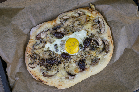 High angel view of an authentic, baked olive flat bread with an egg on top.