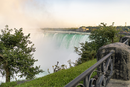 Close-up view of Niagara Falls, clouds of water mist and clear blue water, with tree and handrail in the foreground