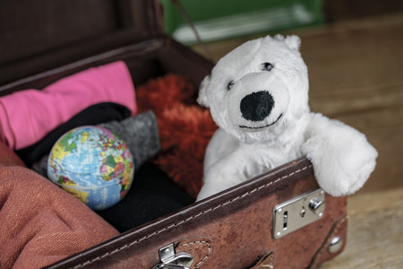 Polar bear toy in suitcase of a traveler, also small globe among the clothes, packed into open vintage brown leather case, viewed in closeup. Traveling with a mascot concept