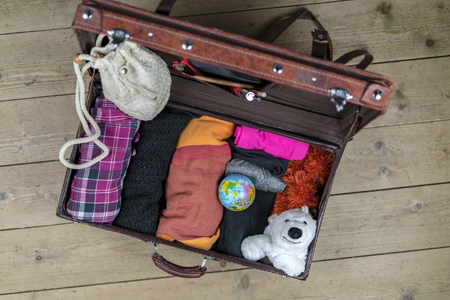 Open vintage suitcase of brown leather packed for the journey with rolled clothes, globe and polar bear toy as a mascot. Case is on the floor and viewed from above