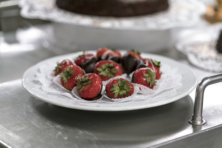 Fresh strawberries served on white napkin on the plate over metal stand in restaurant. Viewed in closeup from the side