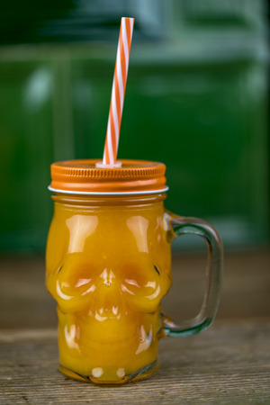 Cocktail or orange juice in close-up in a skull-shaped mason jar glass with handle, with striped straw through stuck metal cup, on the table against green background Standard-Bild