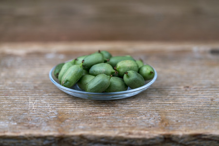 A close up of fresh green kiwis in a bowl on a rustic timber table.