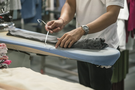 Person is working on grey jeans stretched on ironing board in a laundry shop or at the garment factory