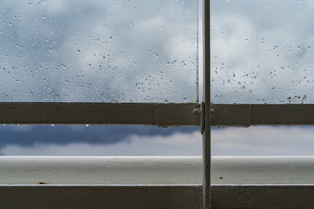 Close up of sea water spray on a glass ship railing with the sky in the background. Standard-Bild