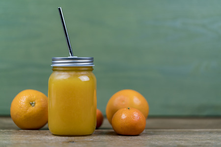 Glass transparent mason jar with orange juice or cocktail with a straw, oranges and tangerines, viewed from the side against green wall background with copy space Standard-Bild
