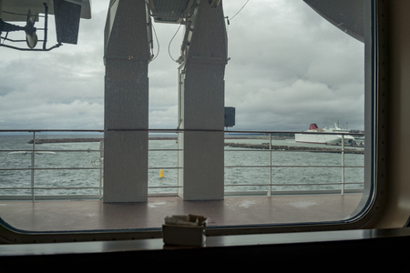 A window view over the deck and harbour from a large, commercial ship.