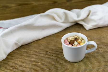 One white cup of cocoa with marshmallows of different colors, next to white fabric napkin nearby on old wooden table surface. Viewed on closeup with copy space