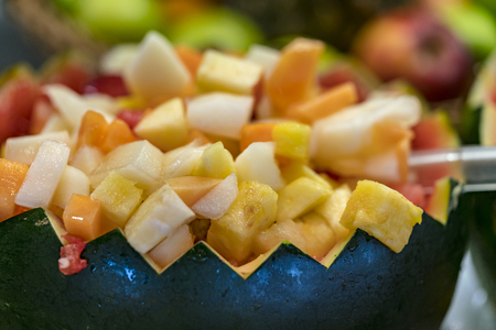 Fruit salad of square slices of colorful tropical fruits served in the decorated watermelon shell used as a green bowl. Viewed in closeup from the side