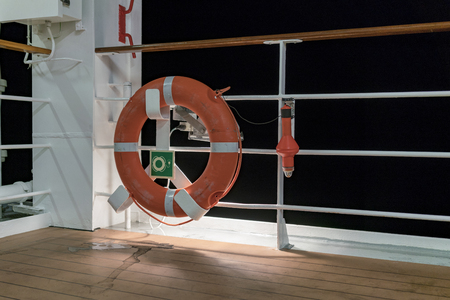 A lifebuoy and beacon on ship deck and railing lit by lights at night time.