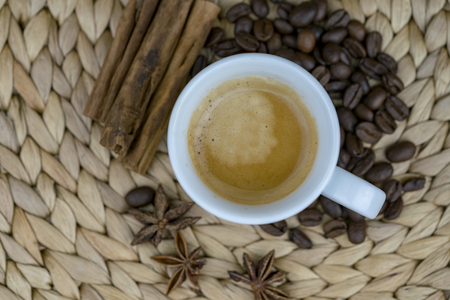 A close up of a mug of coffee on a rustic background with star anise, coffee beans and cinnamon sticks.